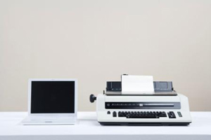 laptop next to typewriter on table